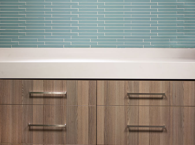 Detail of kitchen mosaic tiles, counter and cupboard finish