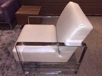 White fabric sofa with chrome armrests
