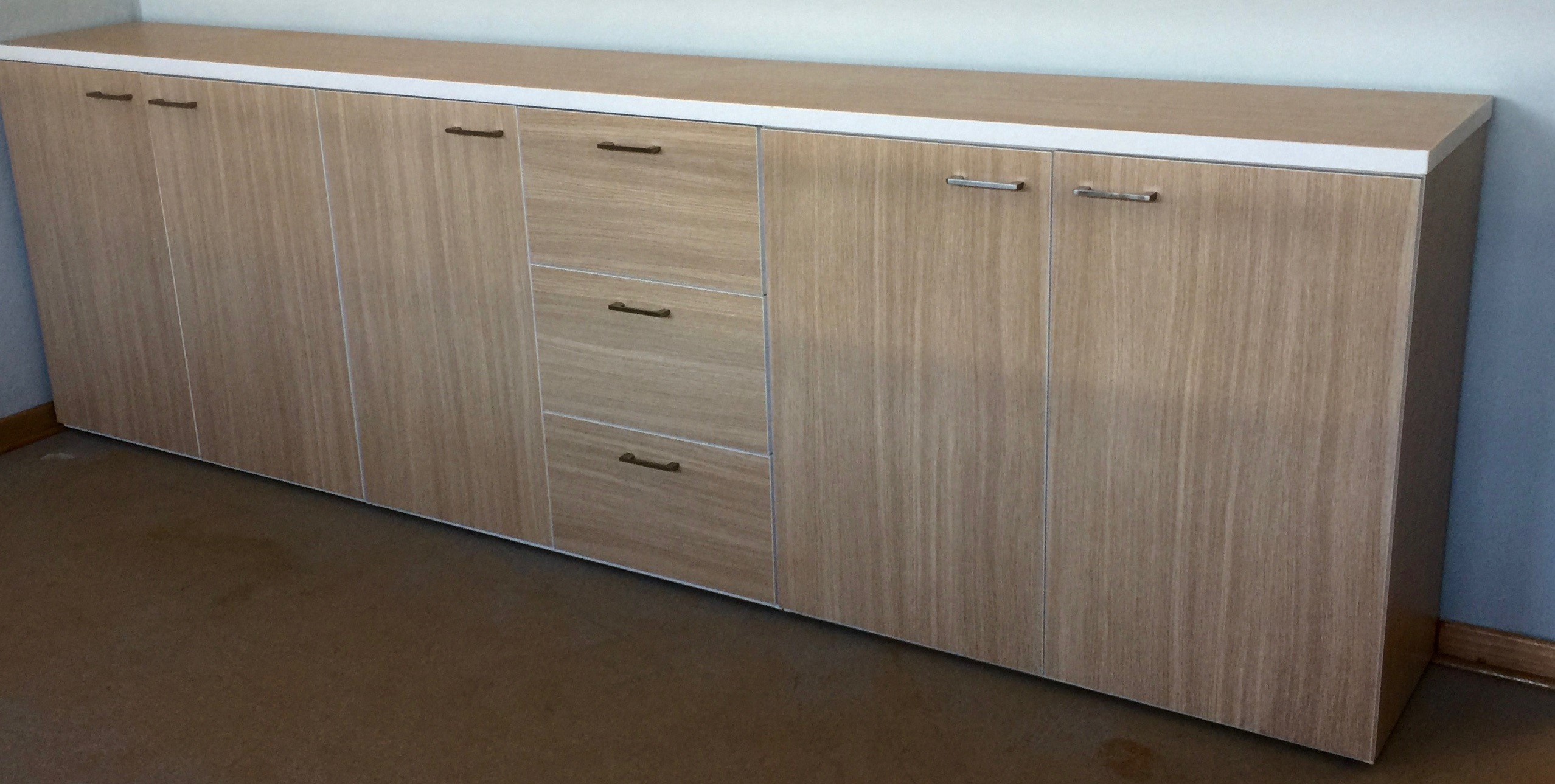 Long Server Storage Unit made up in SummerOak Laminate with White Trim on Edges. Includes drawers and hinged door cupboards with inner shelving. Image