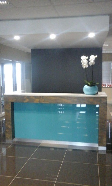 Reception Desk with White Stone Counter top with light blue colour glass front and aluminium trim as skirting Image