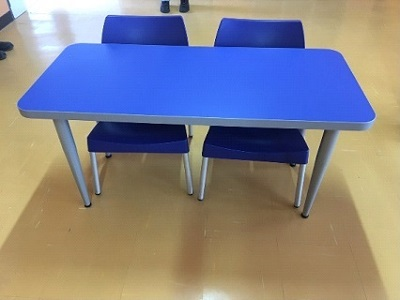 Blue school desk with blue plastic chairs