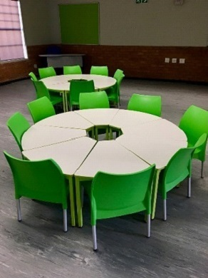 Round learners school desks with green chairs