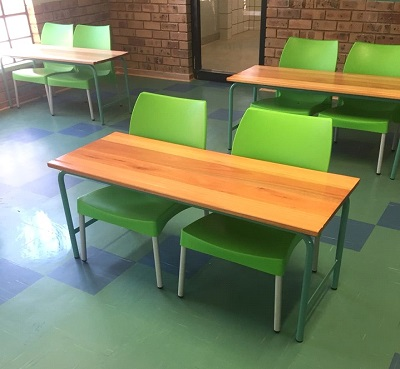 School learners desks with green plastic chairs