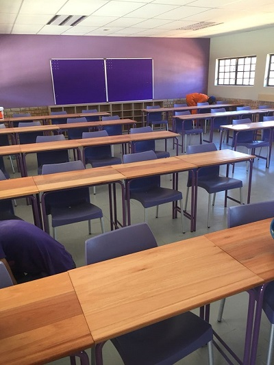 School desks with purple plastic chairs